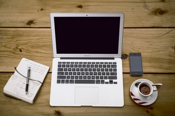 Desk with a note book and a pen with a laptop and a cup of coffee and a phone